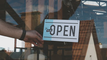 Caucasian Male Turning Sign From Closed To Open On The Entrance Door Of His Small Cafe. Small Business Concept
