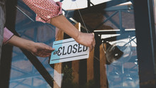 Caucasian Female Turning Sign From Open To Closed On The Entrance Door Of His Small Cafe. Out Of Business