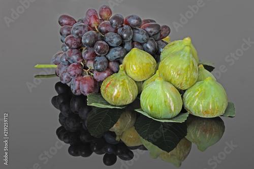 Photo Siyah zemin üzerinde yansımaları ile birlikte , incirler ve kırmızı  üzümler