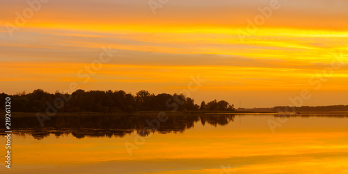 evening water landscape. beautiful orange sunset reflected in lake water