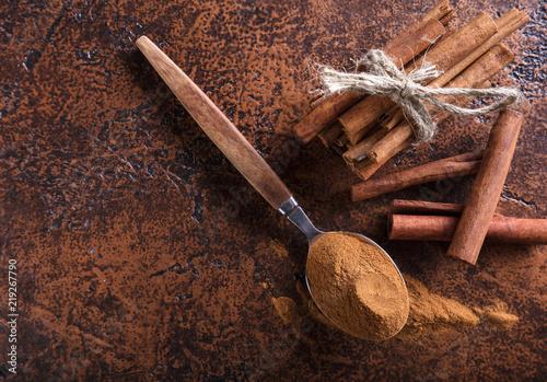 Fotografia Cinnamon sticks and powder in spoon on a old copper table .