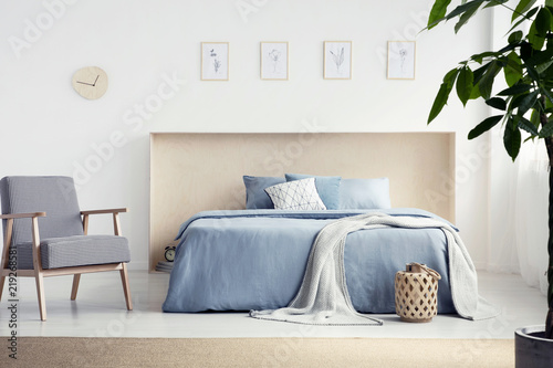 Fototapety, obrazy: Patterned armchair next to blue bed with blanket in natural bedroom interior with posters. Real photo