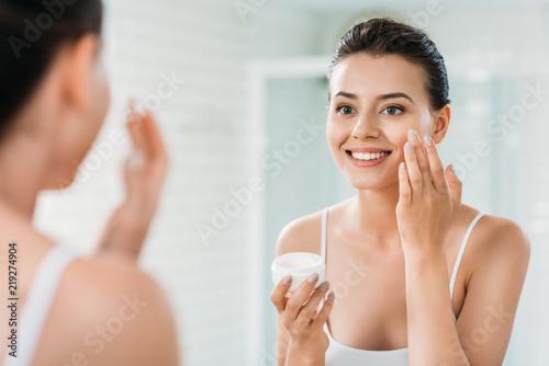 Canvastavla beautiful happy girl applying face cream and looking at mirror in bathroom