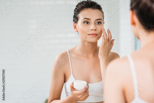 Fotografia beautiful girl applying face cream and looking at mirror in bathroom