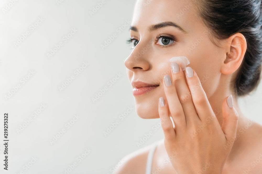 Fototapety, obrazy: beautiful smiling young woman applying face cream and looking away