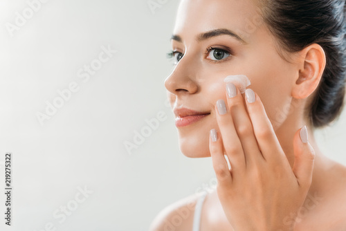 beautiful smiling young woman applying face cream and looking away Canvas Print