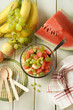 summer fruit salad in the glass bowl - watermelon, peach, grapes, banana and kiwi