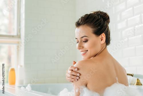 Fotografie, Tablou beautiful smiling young woman relaxing in bathtub with foam