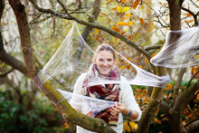 Young Woman Decorating Home Garden For Halloween With Spider Web. Family Celebrating Holiday. Selective Focus On Web