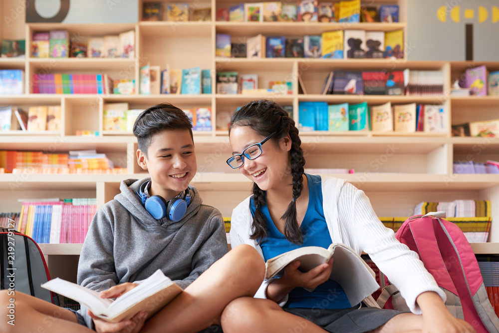 Fototapety, obrazy: Teenage boy and girl sitting in library holding books and smiling on bookshelves background
