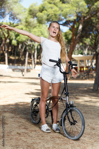 Fotografía  Emotional  teen girl standing near bike ready to go on park ride