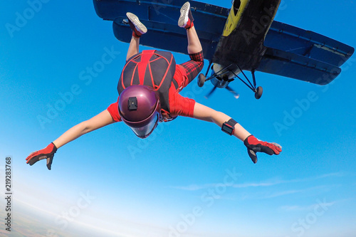 Skidiver in red jumping out of the plane