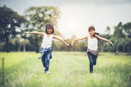 Fototapeta Two little cute girls are running on green grass. Best friends. obraz