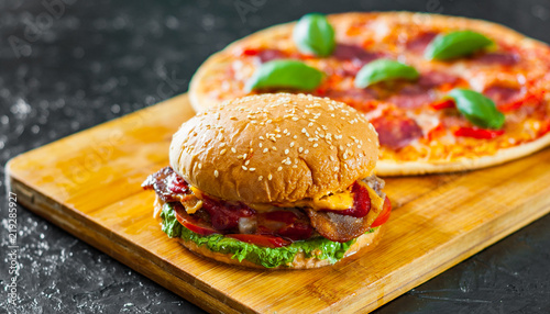 bacon cheese burger with beef patty tomato onion and Pizza with Mozzarella cheese, Ham, Tomatoes, salami, pepper, pepperoni Spices and Fresh Basil © pavel siamionov