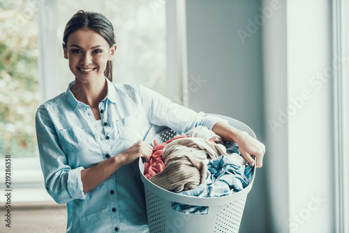 Fototapeta  Young Smiling Woman holds Basket of Clean Clothes
