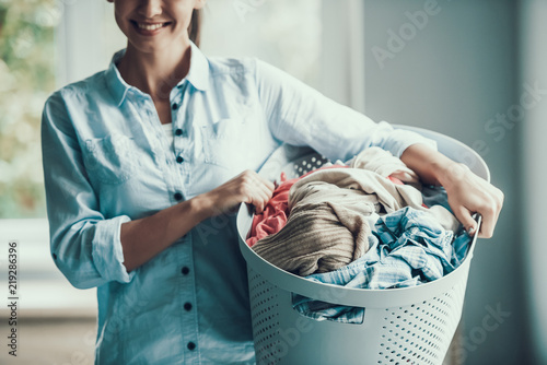 Fotografie, Obraz  Young Smiling Woman holds Basket of Clean Clothes