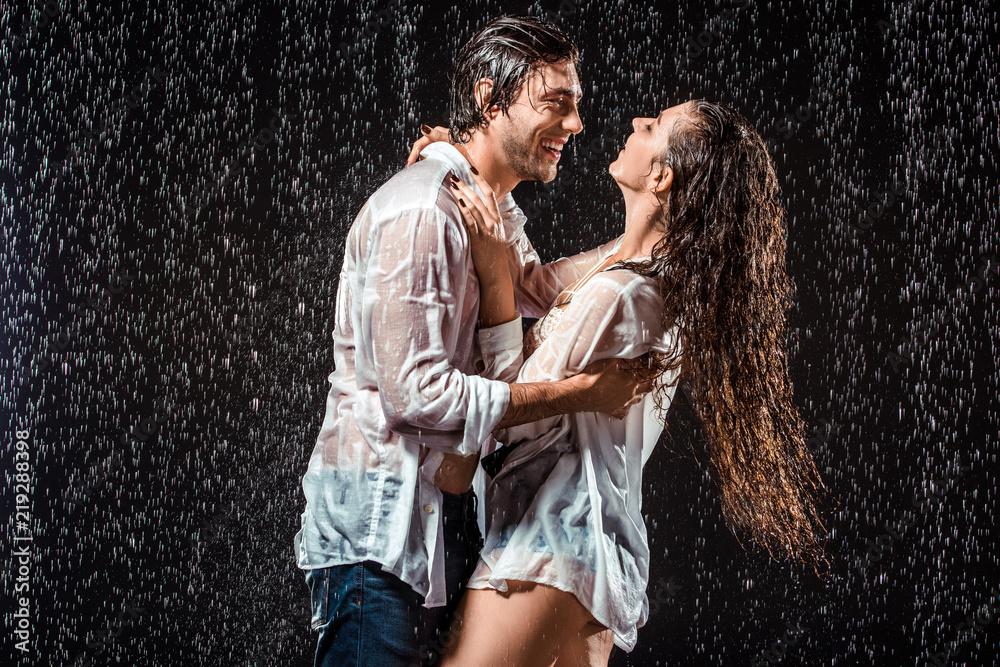 Fototapeta happy wet couple in white shirts standing under rain isolated on black