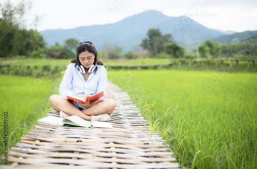 Asian young woman enjoy readbooks on wooden bridge in nature rice