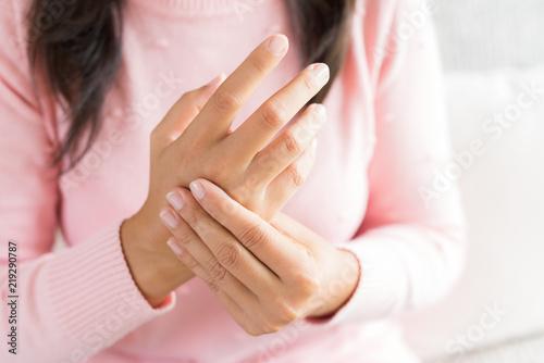 Closeup woman sitting on sofa holds her wrist hand injury, feeling pain Canvas Print