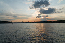 Beautiful Majestic View Of Sun Setting Over A Tranquil River Partly Cloudy Summer Evening. River Coastline On Sides Connected By Bridge In Background Silhouette