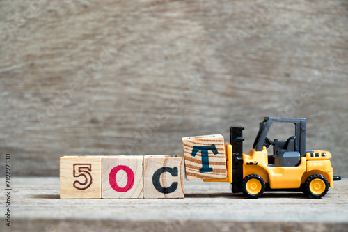 Fényképezés  Toy forklift hold block T to complete word 5 oct on wood background (Concept for
