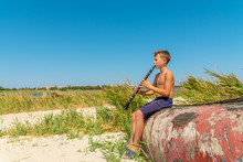 A Boy Is Playing On A Black Clarinet Sitting On An Old Wooden Boat On The Seashore And Looking To The Side, View From The Side.
