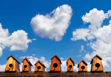 Bird House Nesting On Blue Sky Background