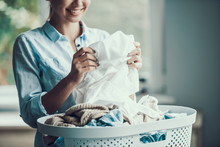 Young Beautiful Smiling Woman Holds Clean Clothes