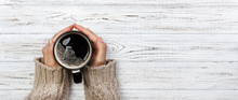 Woman Holding Cup Of Hot Coffee On Rustic Wooden Table, Closeup Photo Of Hands In Warm Sweater With Mug, Winter Morning Concept, Top View. Banner