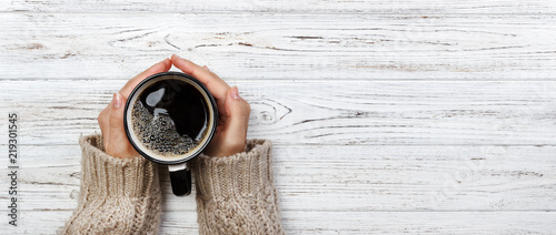 Plakaty do kawiarni woman-holding-cup-of-hot-coffee-on-rustic-wooden-table-closeup-photo-of-hands-in-warm-sweater-with-mug-winter-morning-concept-top-view-banner