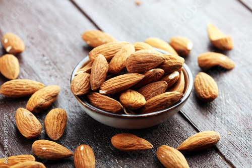 Poster Graine, aromate Almonds on a rustic wooden table and almond in bowl.