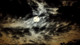 Fototapeta Na sufit - Księżyc na tle ciemnego, nocnego, lekko zachmurzonego nieba