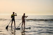 Jeune Couple De Surfeur Au Coucher Du Soleil