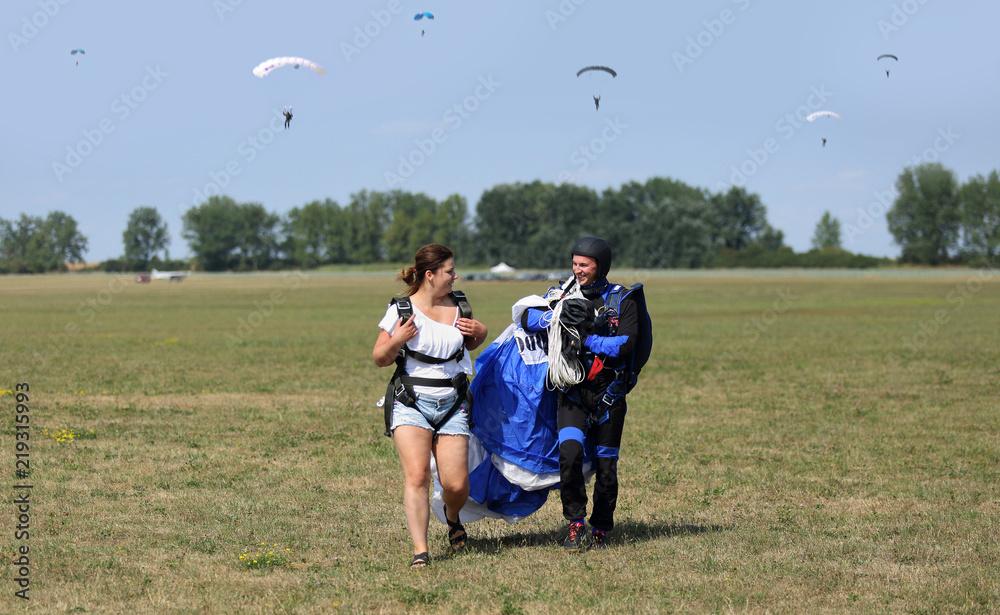 Fototapeta Para młodych ludzi na lotnisku aeroklubu po wykonanych skokach na spadochronach.