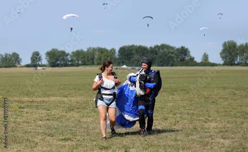 Obraz Para młodych ludzi na lotnisku aeroklubu po wykonanych skokach na spadochronach. - fototapety do salonu