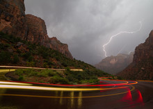 Lightning Lights The Sky And Canyon As A Car Leaves Trails Of Red And Yellow On A Switchback Bend In The Road During An Early Morning Summer Monsoon Storm In Zion National Park.