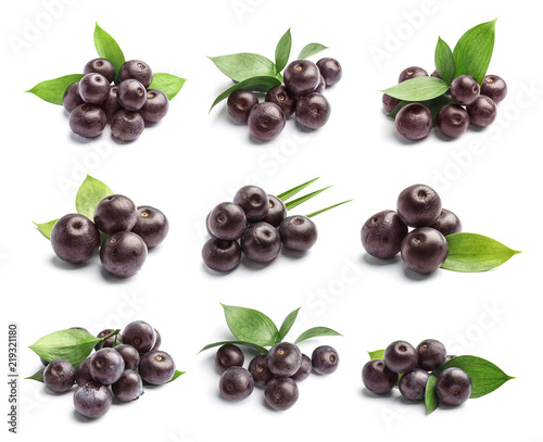 Photo Set with acai berries and green leaves on white background