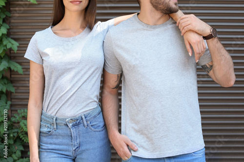 Young couple wearing gray t-shirts near wall on street.
