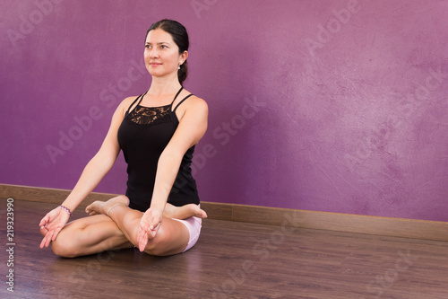 Attractive woman sitting in padmasana with hands in chin mudra. Female yogi in lotus pose with black tank top. Smiling lady practicing yoga meditation indoors. Calm, peace, mindfulness, focus concepts