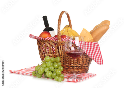 Picnic basket with food and glass of wine on white background