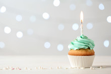 Delicious Birthday Cupcake With Burning Candle And Space For Text On Blurred Lights Background