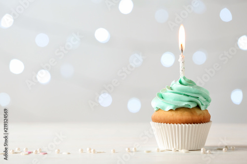 Photo  Delicious birthday cupcake with burning candle and space for text on blurred lig