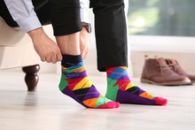Man Putting On Stylish Socks I...