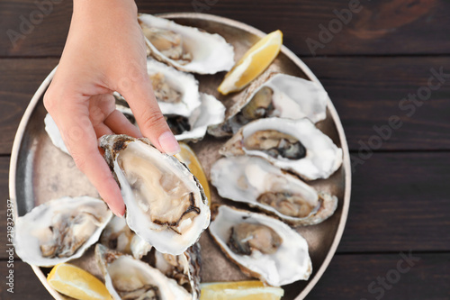 Top view of woman with fresh oyster over plate, focus on hand