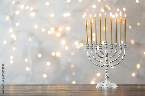 Obraz na plátně Hanukkah menorah with candles on table against blurred lights