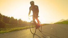 LENS FLARE: Intense Male Biker Pedals His Road Bicycle On A Summer Sunny Evening