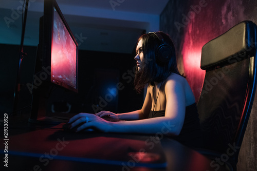 Photo  girl gamer in headphones and with a keyboard and mouse in her hands playing netw
