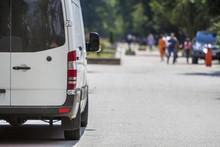 Back View White Passenger Medium Size Commercial Luxury Minibus Van Parked On Summer City Street.