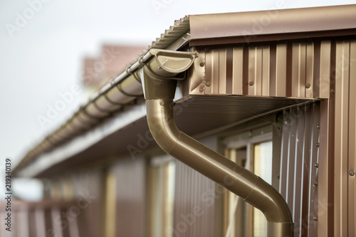Photo  Close-up detail of cottage house corner with metal planks siding and roof with gutter rain system