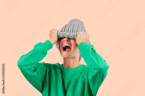 Fotografie, Obraz  Crying emotional angry woman is pulling wool hat over her eyes